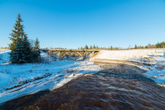 Snowy winter river landscape with metal bridge Stock Images