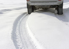 Snowy winter road behind an  car Royalty Free Stock Image