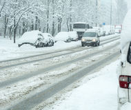 Snowy winter road with cars  in snow storm Royalty Free Stock Image
