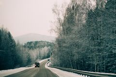 Snowy winter road among frozen forest after sleet. Cold weather, snowstorm, bad visibility. Moscow area. Winter road among the snow-covered forest Royalty Free Stock Image