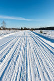 Snowy winter road with tire markings Royalty Free Stock Photos