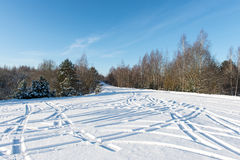 Snowy winter road with tire markings Stock Photo