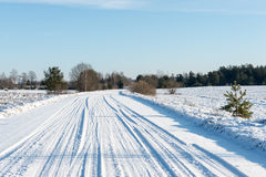 Snowy winter road with tire markings Royalty Free Stock Photography