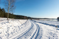 Snowy winter road with tire markings Royalty Free Stock Image
