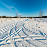 Snowy winter road with tire markings Stock Images