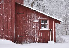 Snowy winter scene of an old shed. Snow covered red shed with window, shovel and wire star royalty free stock photography