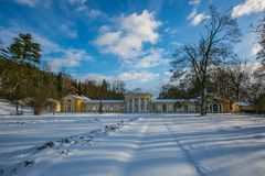 Snowy winter scene of yellow building of Ferdinand colonnade. With mineral water at spa town Marienbad, Czech Republic, park with trees, long shadows, bright stock photos