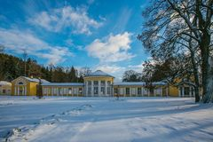Snowy winter scene of yellow building of Ferdinand colonnade with mineral water at spa town. Marienbad, Czech Republic, park with trees, shadows on ground stock photo