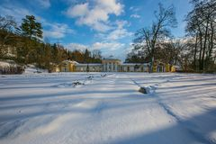 Snowy winter scene of yellow building of Ferdinand colonnade. With mineral water at spa town Marienbad, Czech Republic, park with trees, long shadows, sunny day royalty free stock photos