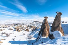 Snowy winter time at three Graces, three Beautifuls uc guzeller rock hills in Devrent valley Cappadocia, Nevsehir, Turkey. royalty free stock photo