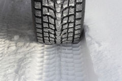 Snowy-Winterstraße voran ein Auto Stockfotografie