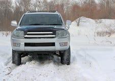 Snowy-Winterstraße voran ein Auto Stockfotos