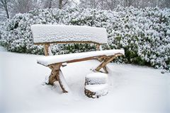 Snowy wooden bench in the forest royalty free stock photos