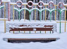 A snowy wooden bench and metal hedge behind on the winter background of fence stock photography