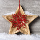 Snowy wooden star with christmas ornament Royalty Free Stock Photography