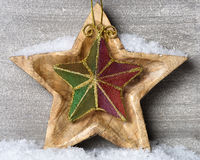 Snowy wooden star with christmas ornament Stock Photos