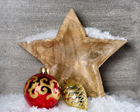 Snowy wooden star with christmas ornament Stock Photography