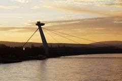 The SNP bridge in Bratislava, Slovakia. The SNP bridge with UFO tower restaurant in Bratislava, Slovakia at sunset time stock photo