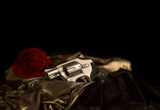 Snub Nose Revolver laying on Gold Satin Stock Photo