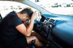 Snubblar den trötta unga stiliga mannen för Closeupståenden med den korta uppmärksamhetspännvidden som kör hans bil efter lång ti royaltyfria bilder