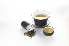 Snuff cup with green, flower tea, gaiwan and a tea cup. On a white background Stock Photo
