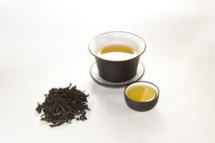 Snuff cup with green, flower tea, gaiwan and a tea cup. On a white background Stock Photos