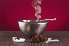 Snuff rolling, ashtray and cigar Stock Photography