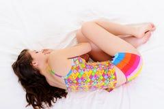 Snuggle do sono da mulher nova na cama Imagens de Stock