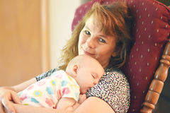Snuggle Time. A baby sleeping on a woman`s shoulder in a rocking chair.  She naps peacefully while being snuggled and rocked Stock Images