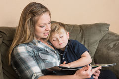 Snuggle Time. A young boy snuggles into his mother as she reads him a book stock photos