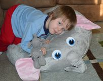 Snuggling Elephant Toddler. Elephant-loving toddler snuggles his stuffed pillow he calls an elephant nest Royalty Free Stock Photo