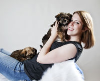 Snuggling with puppy. A pretty girl snuggling with affectionate puppies royalty free stock photos
