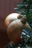 Snuisterijen van Sparkly de gouden Kerstmis op boom Stock Foto's