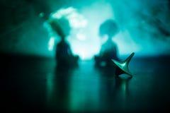 Snurr för totemsnurröverkant som vacklar och stoppar Snurröverkant på spegelyttersida med tonat rökbakgrundsljus Karusell in Arkivbild