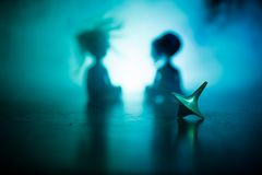 Snurr för totemsnurröverkant som vacklar och stoppar Snurröverkant på spegelyttersida med tonat rökbakgrundsljus Karusell in Arkivfoto