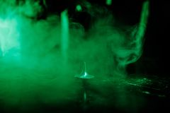 Snurr för totemsnurröverkant som vacklar och stoppar Snurröverkant på spegelyttersida med tonat rökbakgrundsljus Karusell in Royaltyfri Bild