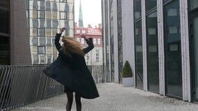 Snurrande för ung kvinna glatt på gatan stock video
