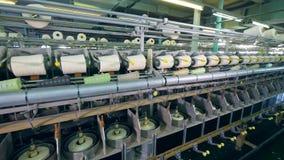 Snurrmaskiner fungerar på textilfabriken som köar tråden på clews stock video