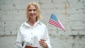 Snygg amerikansk flagga för USA för kvinnainnehavmedborgare som ler på tegelstenbakgrund stock video