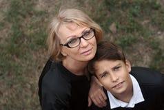 Snygg, singel-förälder mamma och tonårig son i parkera foto royaltyfria foton