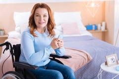 Snygg vaken rörelsehindrad kvinna som rymmer hennes telefon Royaltyfri Bild