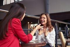 Snygga kvinnlig som berättar roliga berättelser, medan tycka om kaffe Arkivfoton