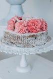 Snylta den dekorerade bröllopstårtan med blommor på en vit sockel Arkivbild