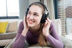 Soñando a la muchacha magnífica que se acuesta, disfrutando de escuchar la música relajante Fotos de archivo