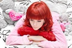 Soñando a la mujer joven en cama con los juguetes que miran abajo Foto de archivo libre de regalías