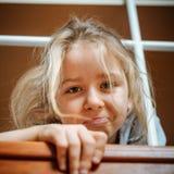 Soñoliento niña linda divertida con el pelo largo que presenta en casa fotografía de archivo