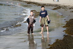 Soaked. Two brothers walking along a beach having got soaked by the sea Royalty Free Stock Image