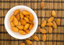 Soaked almonds in a bowl against a straw mat Royalty Free Stock Photography