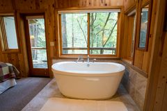 Soaking Bath Tub in Cabin. Soaking bath tub in a cabin in the national forest. This bathtub is oversized and luxurious stock image