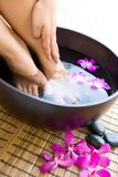 Soaking feet in bowl of floral scented water Stock Photography